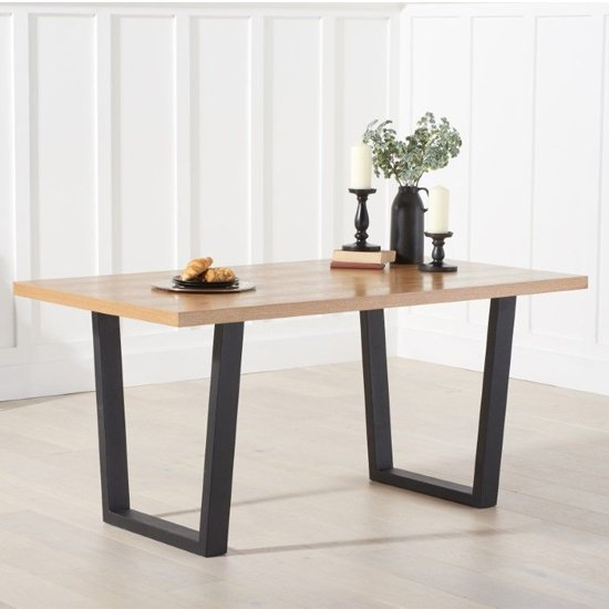 View Olinom wooden dining table in oak with black metal legs